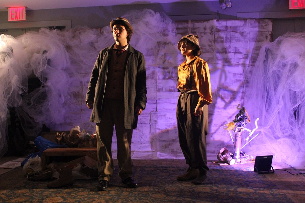 "Charles Soto as Vladimir (left) and Mikaela Baker as Estragon (right) stand in front of  Waiting for Godot 's famous tree, created here with the shadow cast by a sculpture made from trash. ""[Bryan Hunt] gave me lots of creative liberty,"" set designer Jane Gendron said. ""When I came up with an idea, his answer was almost always, 'let's go for it.'"" II Photo Credit: Audrey Pickett"