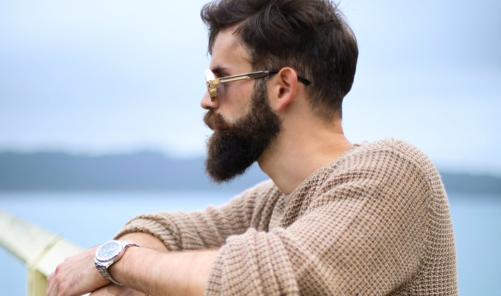 Man wearing brown sweater standing on wooden dock. || Photo by  Jonathan Zerger  on  Unsplash