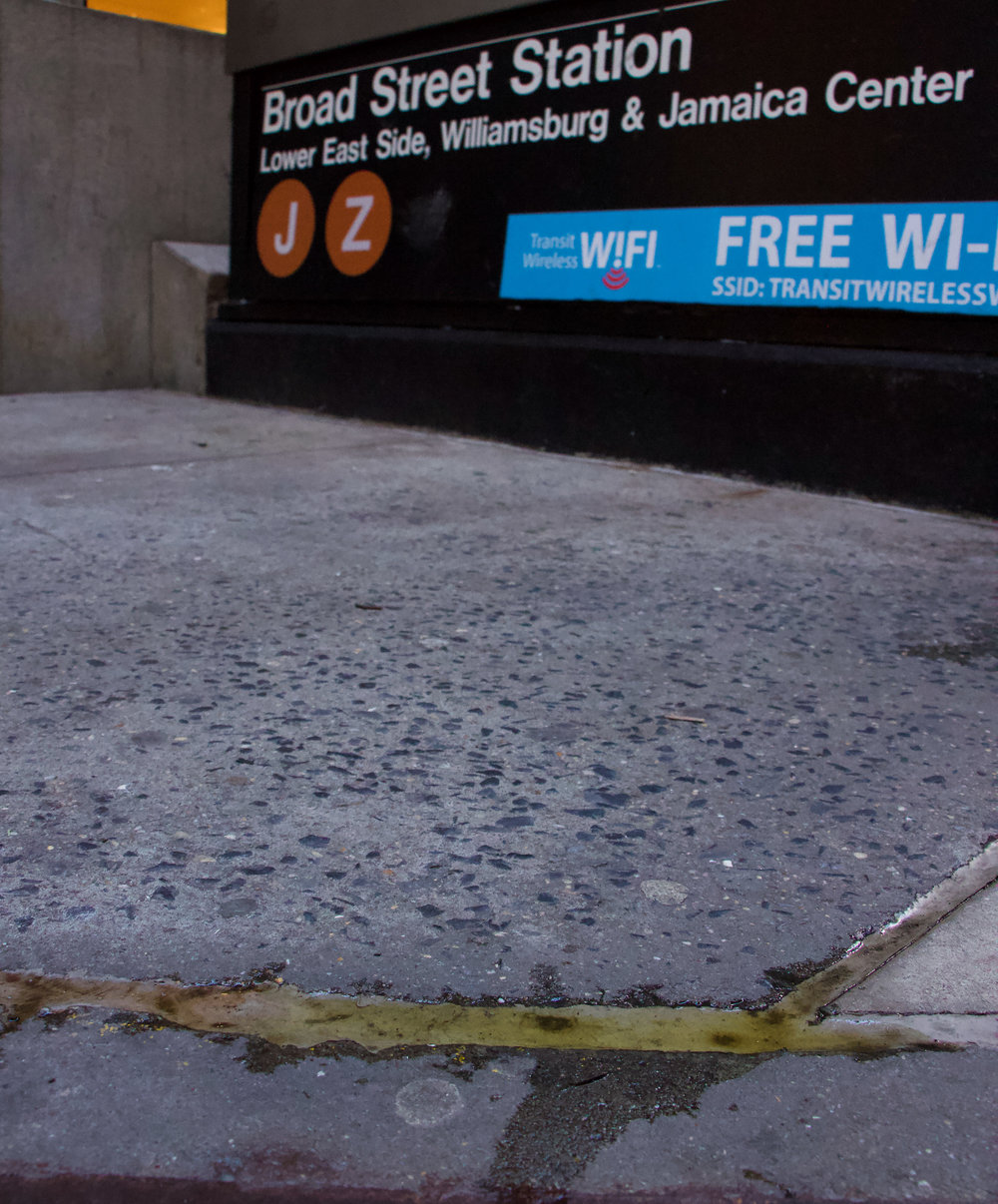 A yellow-liquid substance lies in the crevices outside the J/Z subway station at Broad Street. || Photo credit to Gabriela Kressley.