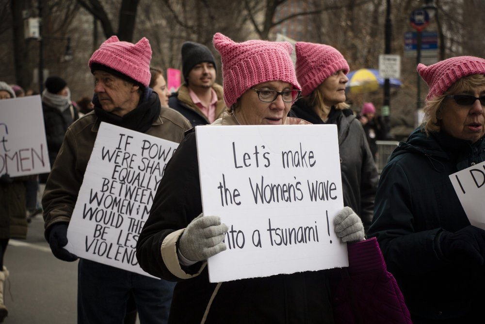 """A women holds a sign that reads """"Let's make the Women's wave into a tsunami"""" at the NYC Women's March on 59th Street on Saturday, January 19, 2019. 