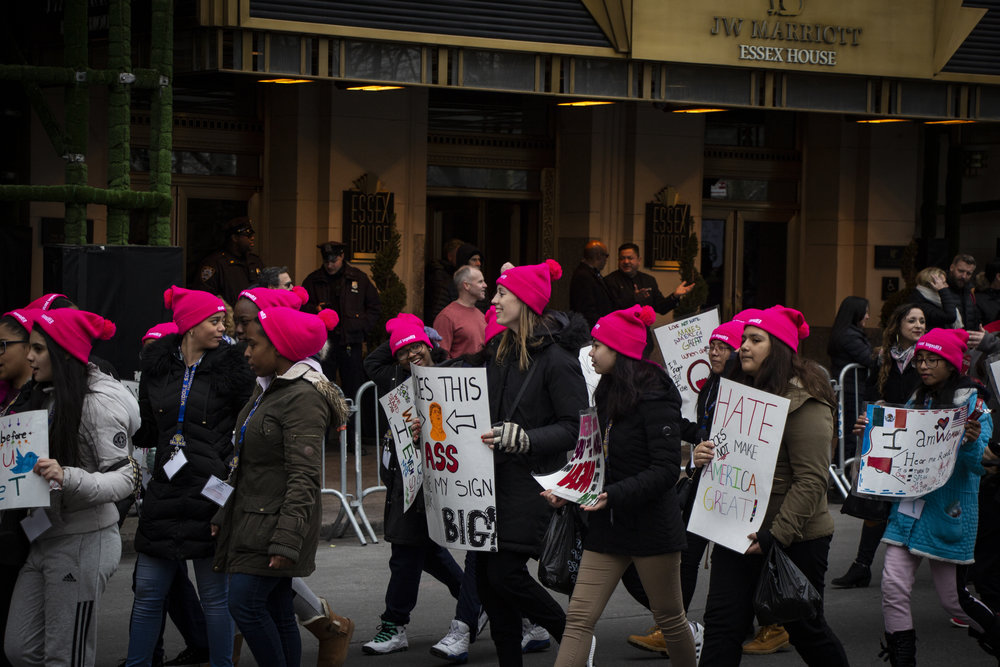 A group of girls wearing pink hats walk in the Women's March NYC. || Photo credit to Bernadette Berdychowski