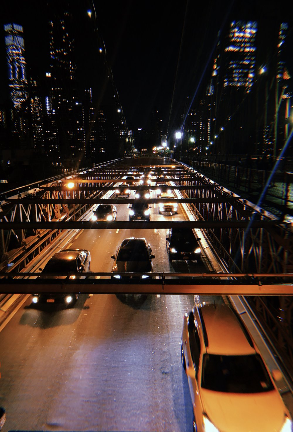 Ubers and Lyfts spotted on the Brooklyn Bridge at night.    Photo credit to Hannah Mallard