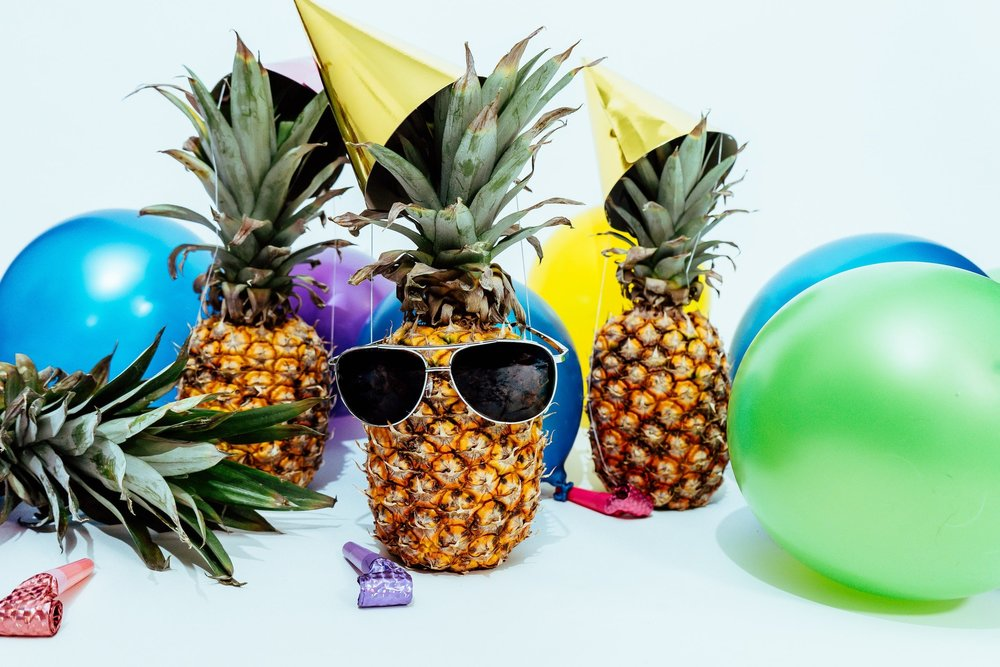 3 pineapples celebrating. One's wearing glasses and there are balloons on the floor