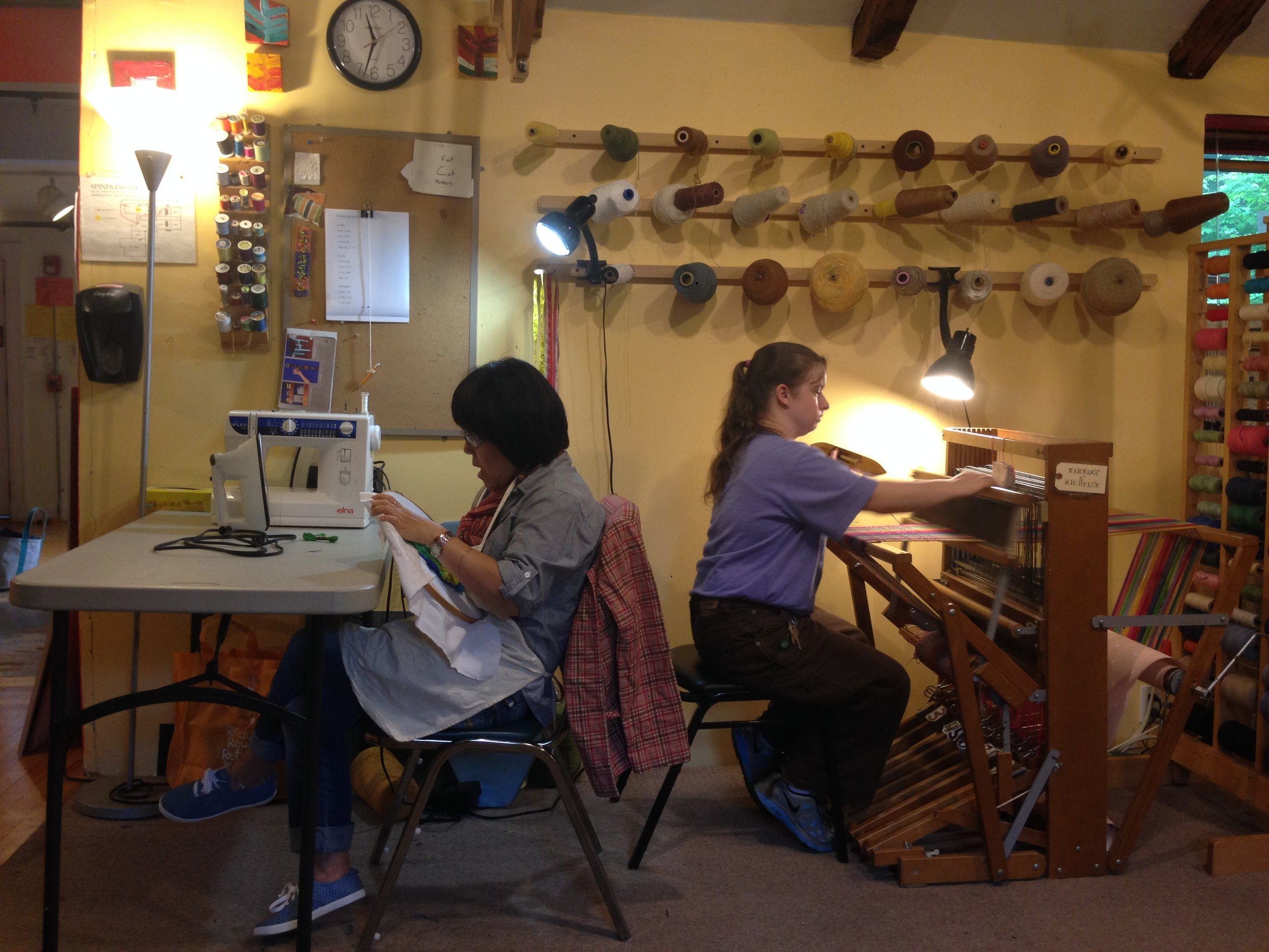Kim and Michelle sewing and weaving, respectively