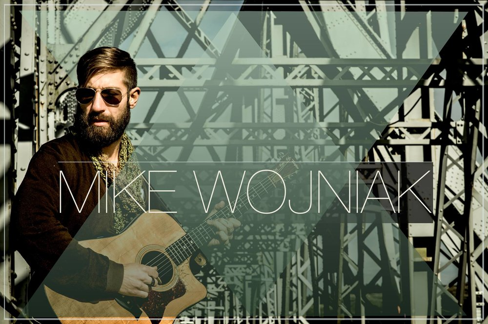 Mike Wojniak with his guitar on a bridge.