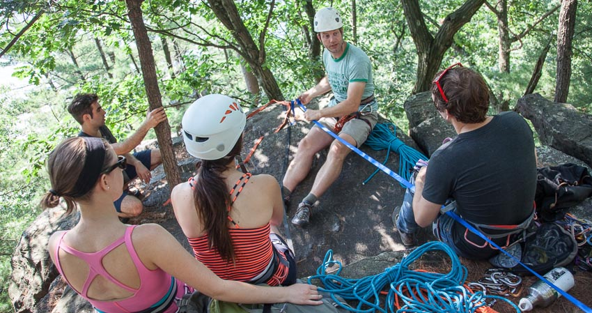 Lead guide teaching a climbing anchors class as 4 students look on