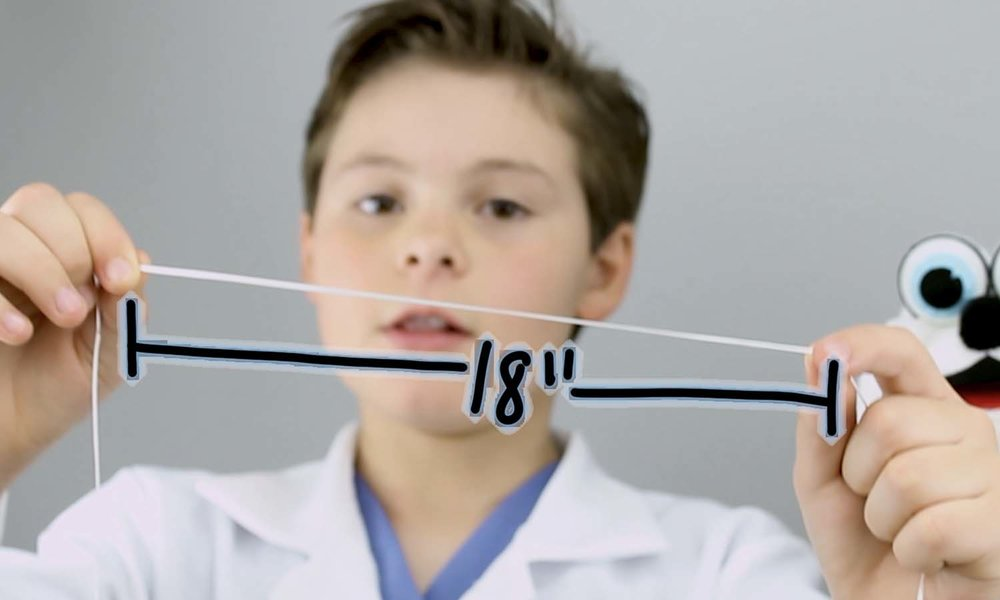 boy holding 18 inches of dental floss.jpg