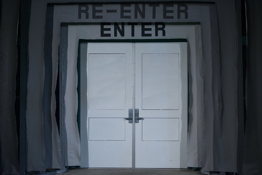 ENTER-RE-ENTER (proscenium) , A series of 5 fabric banners were built into the threshold of the site. A pattern of ascending gray coloring radiated from the white door, each banner adorned with the text ENTER alternating with the text RE-ENTER, radiating outward in a conversely sequenced gray scale so that the center banner has the same color grey for the text as it does for the background, rendering it nearly imperceptible.