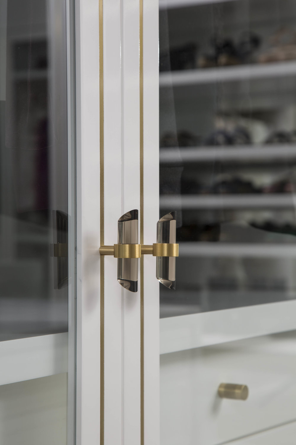 CUSTOM BRASS INLAY COMPLEMENTS BRUSHED BRASS AND SMOKE GLASS HARDWARE.