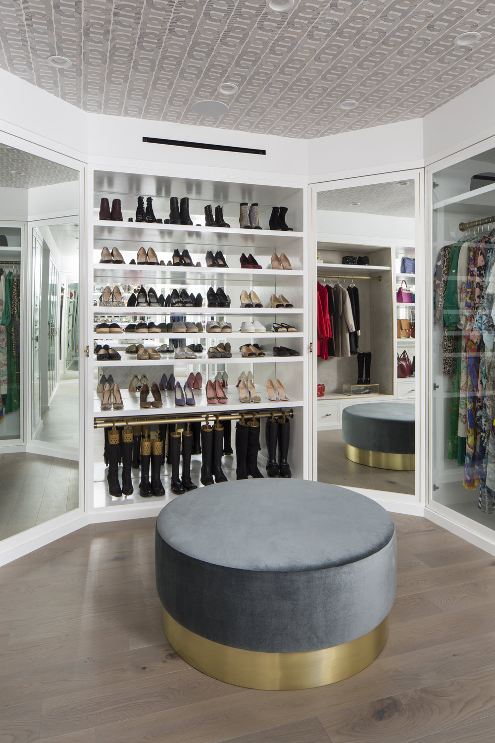 CORNER MIRRORED CABINETS CONCEAL ADDITIONAL HANGING SPACE FOR THE CLIENT'S SEASONAL ITEMS, AND A FLOOR TO CEILING SHOE DISPLAY CREATES THE ULTIMATE IN-HOME BOUTIQUE.