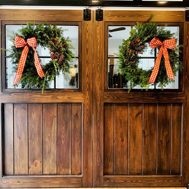 Beautiful split sliding doors between a kitchen and living room. The Christmas wreaths add a perfect seasonal touch! #barndoors #slidingbarndoors #farmhouse #farmhousestyle #farmhousedecor #farmhousechristmasdecor #barndepot #handcrafted #lancasterma #boltonma
