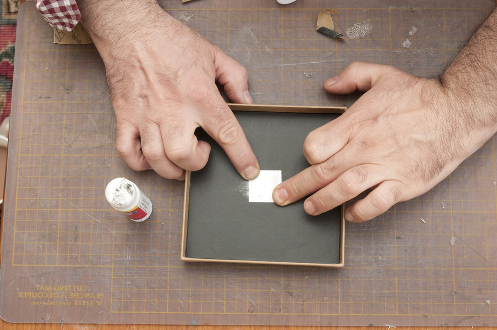 Apply glue to the aluminium containing your pinhole. Make sure that the glue does not cover the pinhole and position the pinhole over the hole you bored earlier