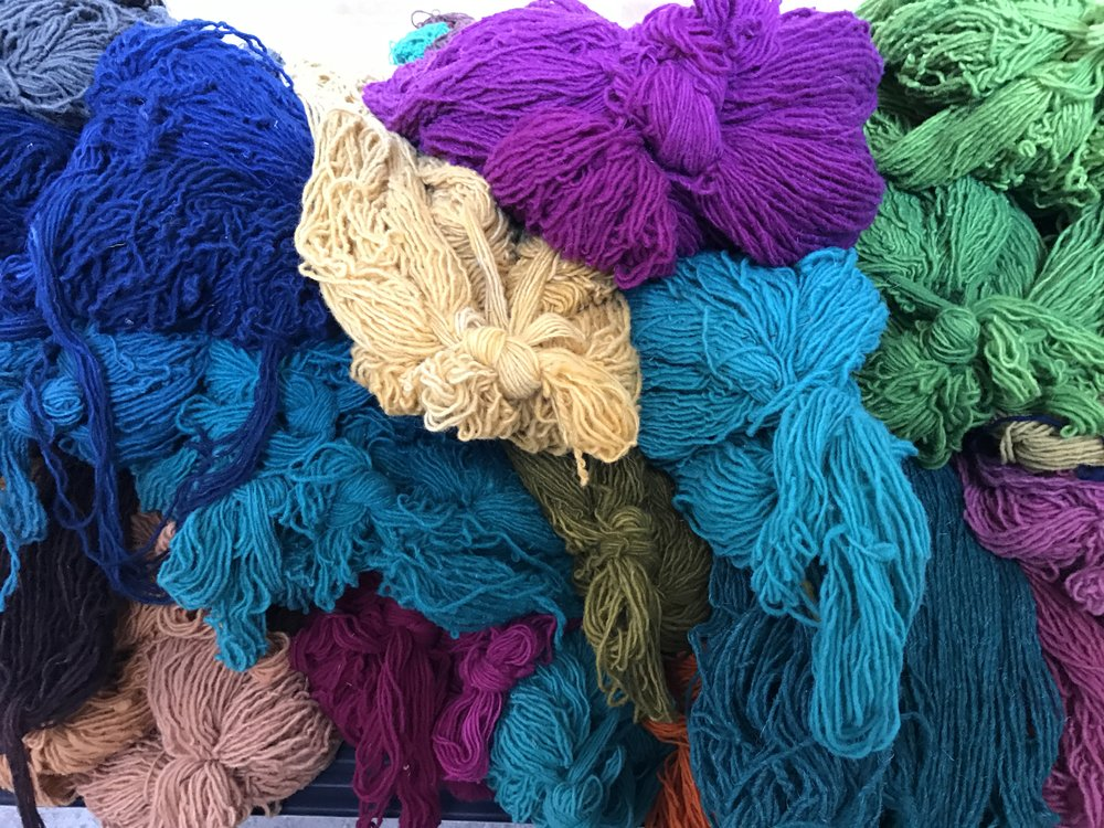 Dyed wool piled high on a queen-size bed.