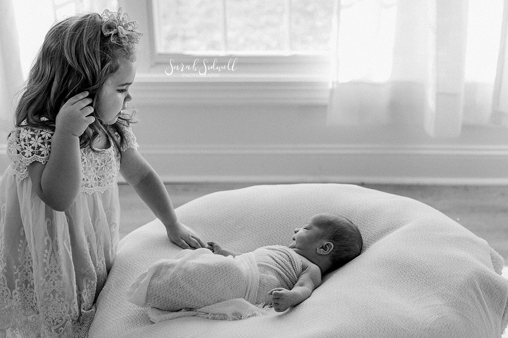 A little girl checks on her newborn brother  | Sarah Sidwell Photography | Newborn Love