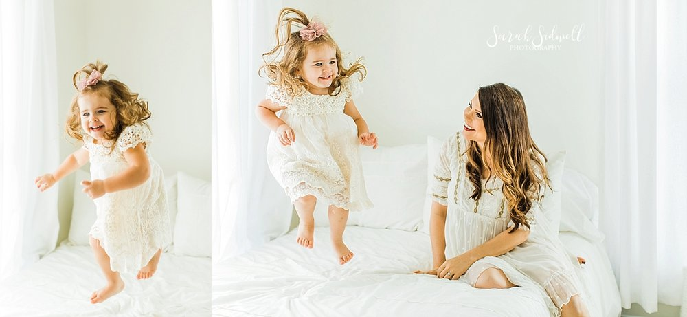 A little girl jumps on the bed  | Sarah Sidwell Photography | Newborn Love