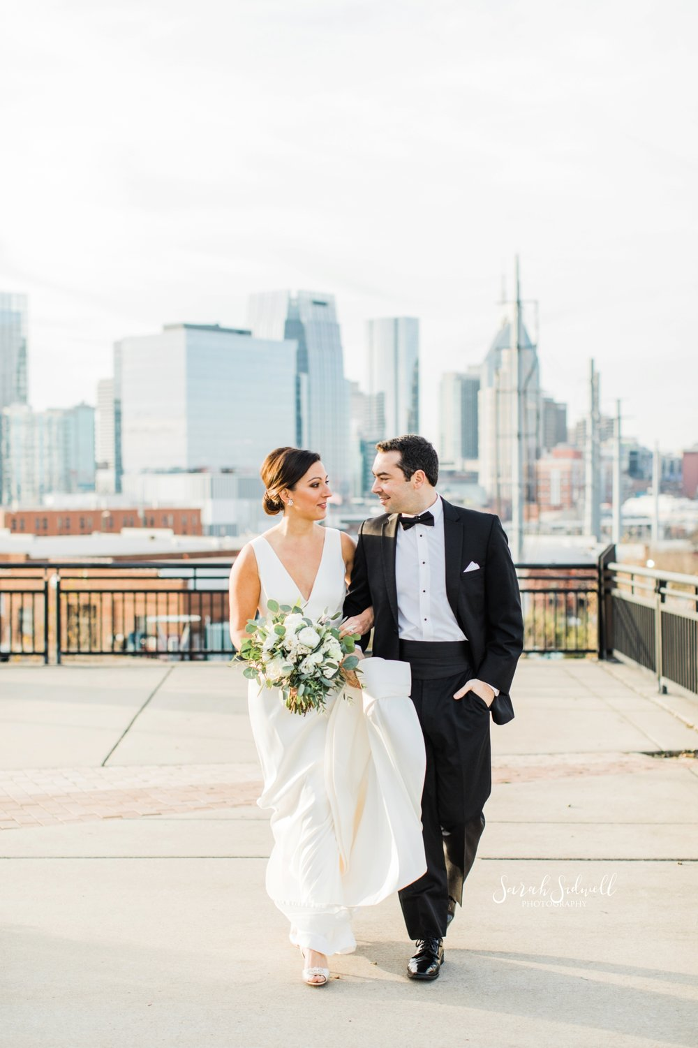 A bride and groom walk together | Sarah Sidwell Photography | The Bell Tower