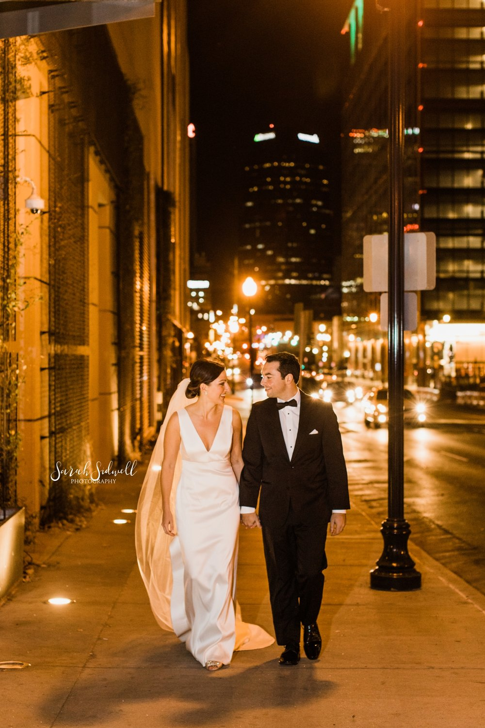 A bride and groom take a walk on a city street | Sarah Sidwell Photography | The Bell Tower