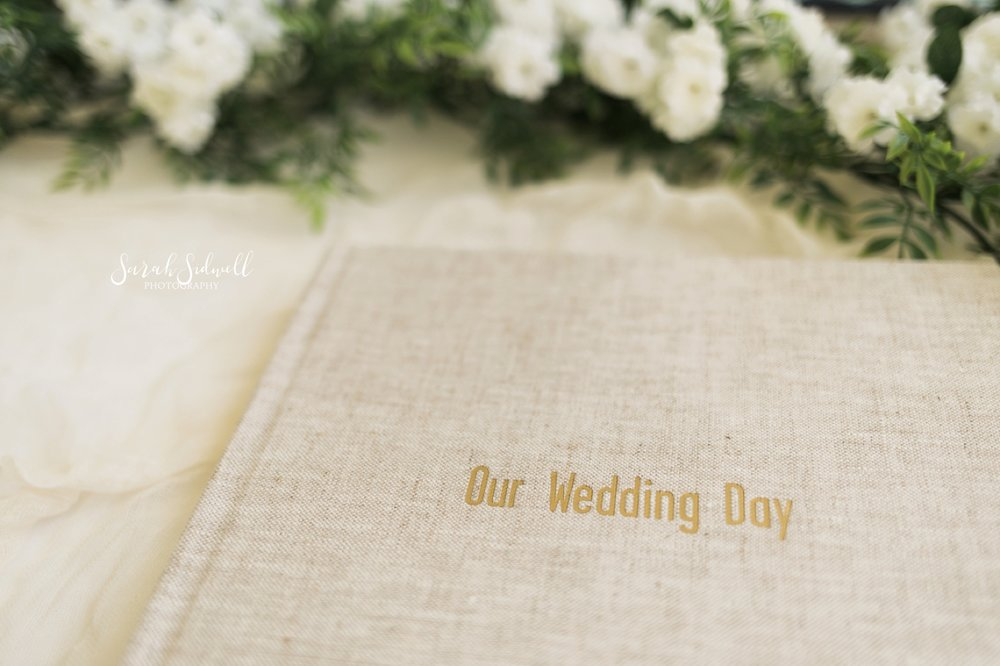 A wedding album is displayed with gold etching on the front.