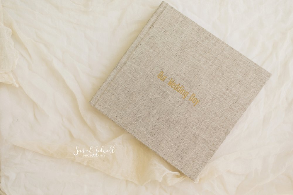 A high quality wedding photo album sits on a table as an example of what the photographers offers to her clients.
