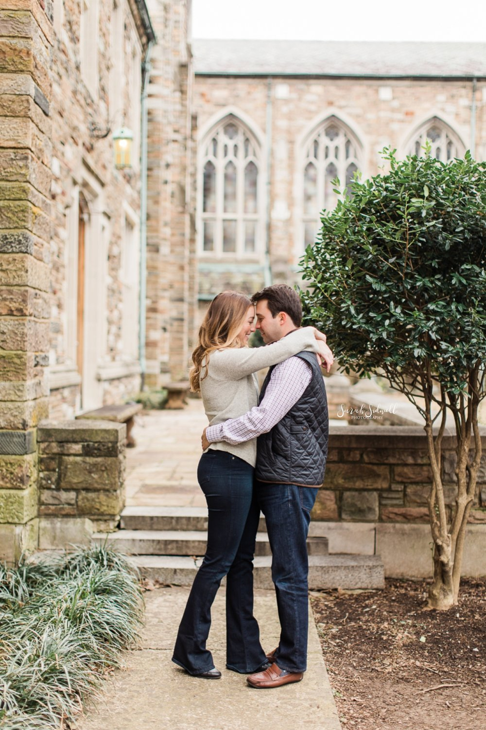 A couple hug in a park in front of the camera of their Nashville Engagement Photographer.