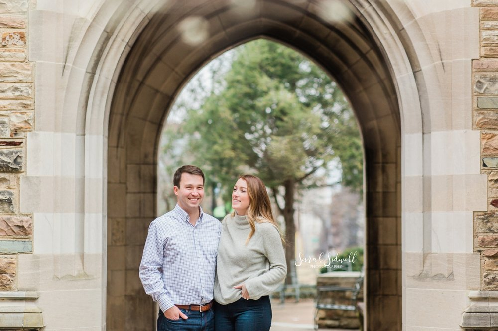 A couple stand under an archway