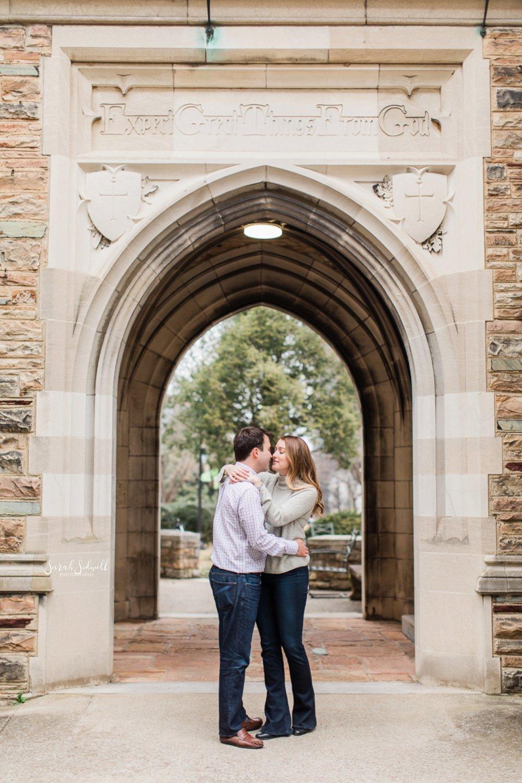 A couple kiss beneath an archway.