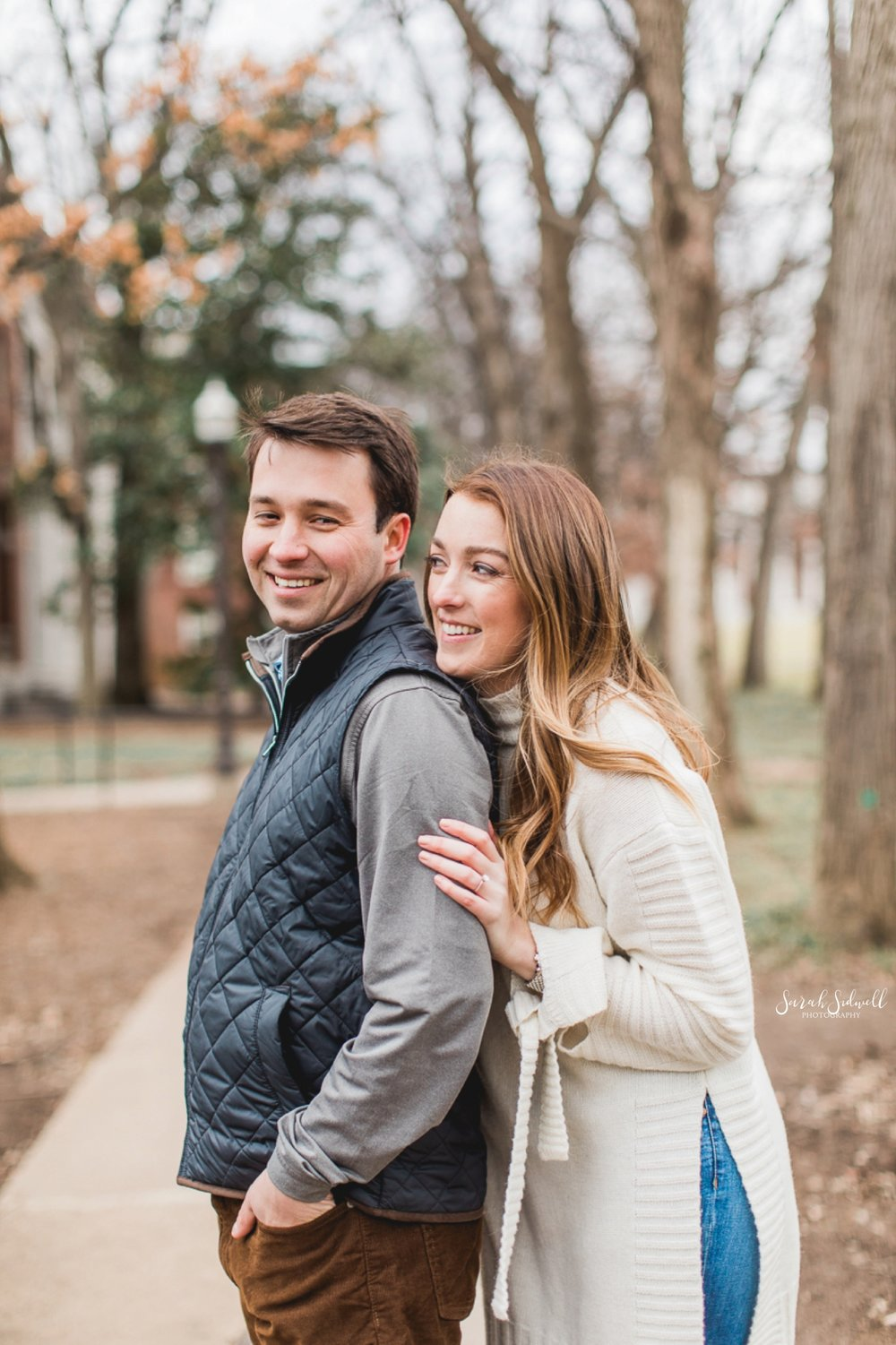 A woman leans into her fiance from behind.