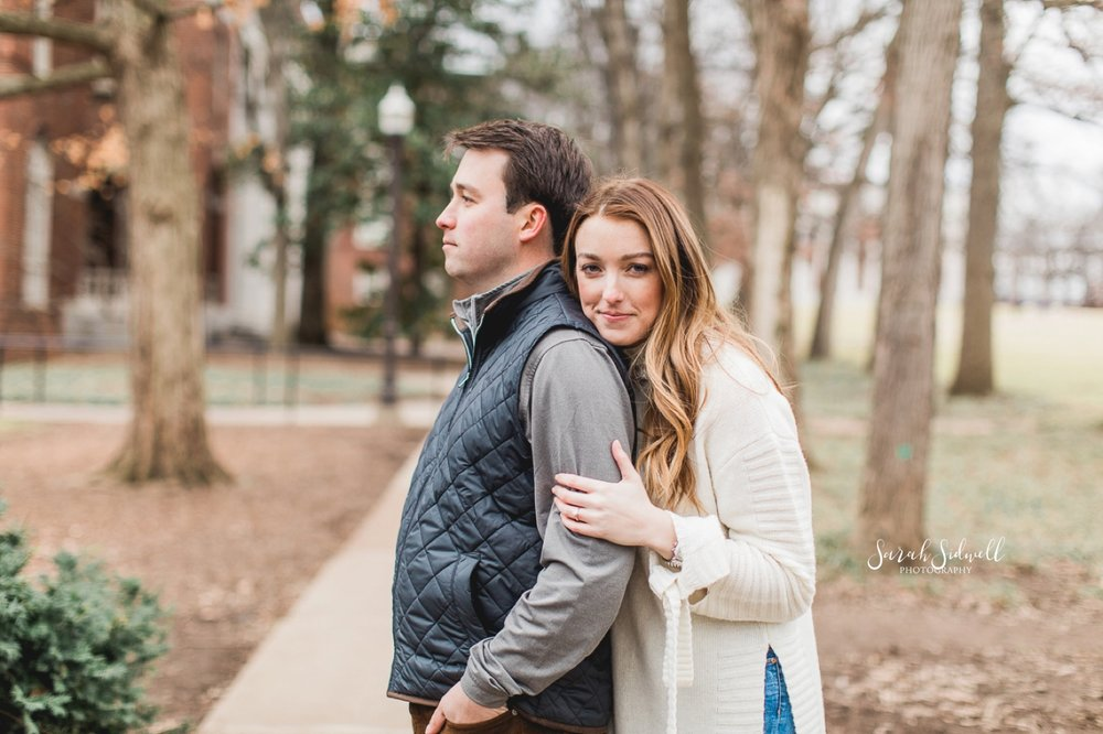 A woman hugs her fiance from behind.
