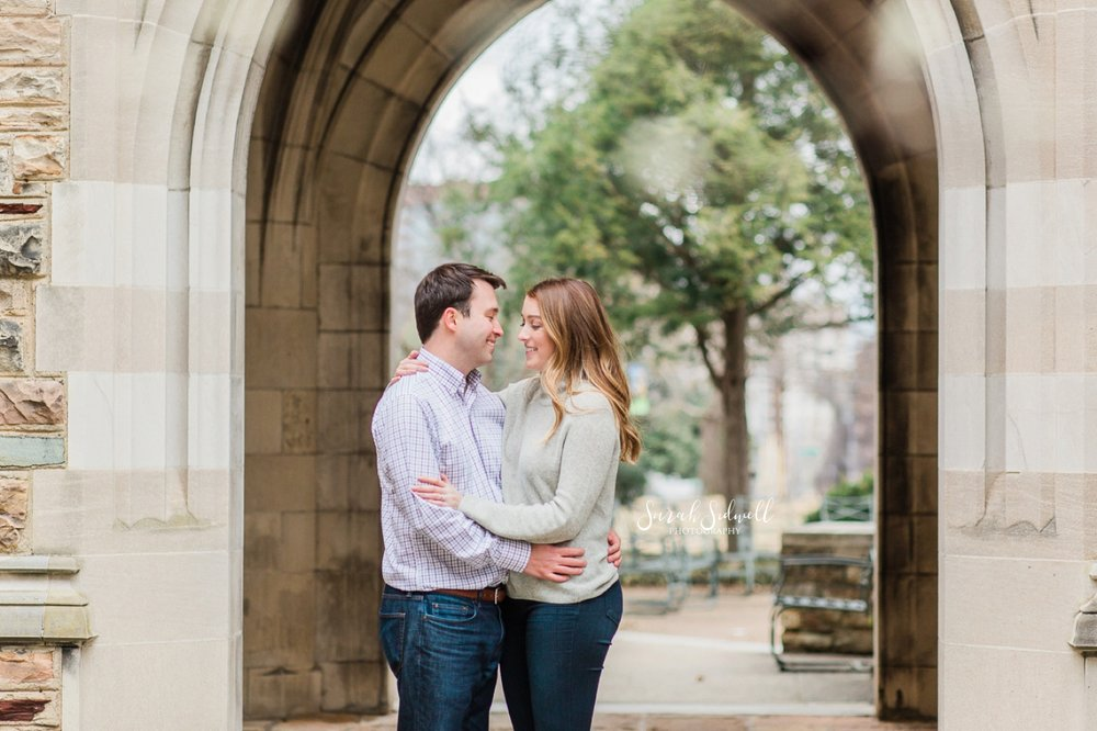 A couple share a close moment under an archway.