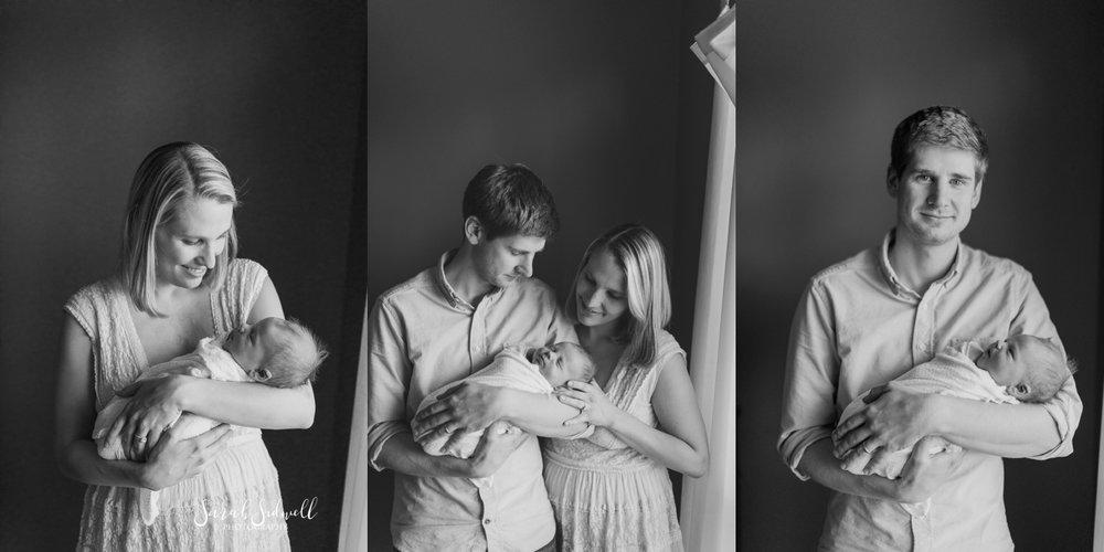 A couple admire their newborn baby.