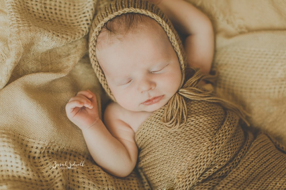 A newborn sleeps in a bonnet.