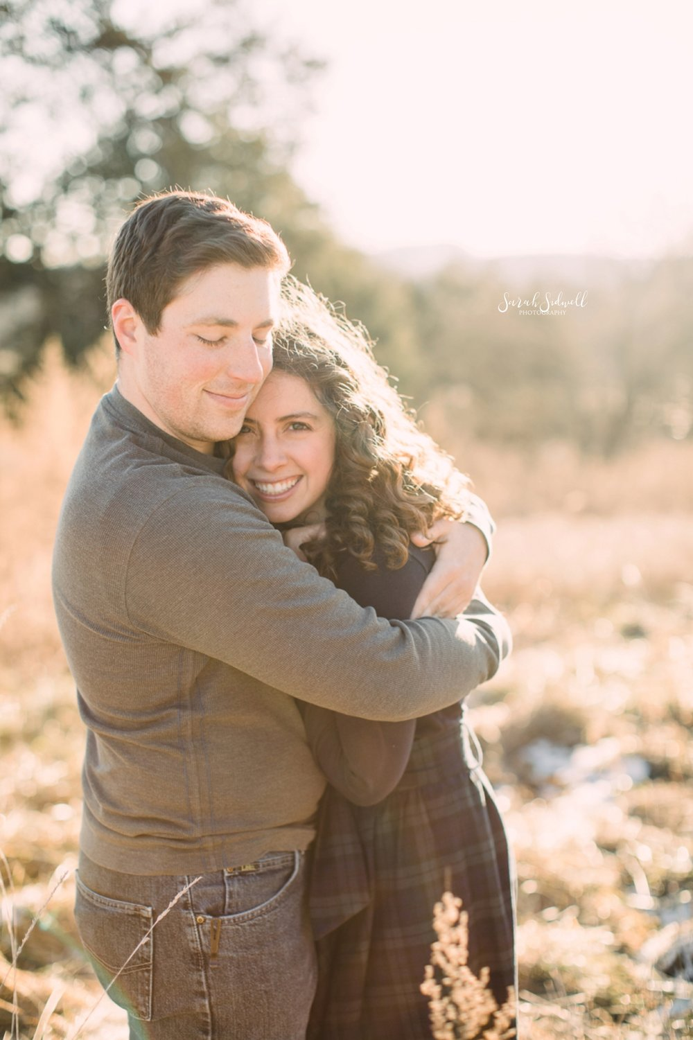 A man hugs his fiance for a photo taken by an Engagement Photographer in Nashville.