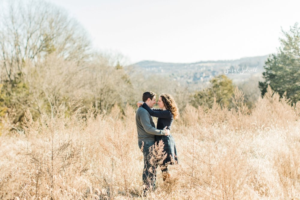 A couple dance in a field for their photo session by an Engagement Photographer in Nashville.