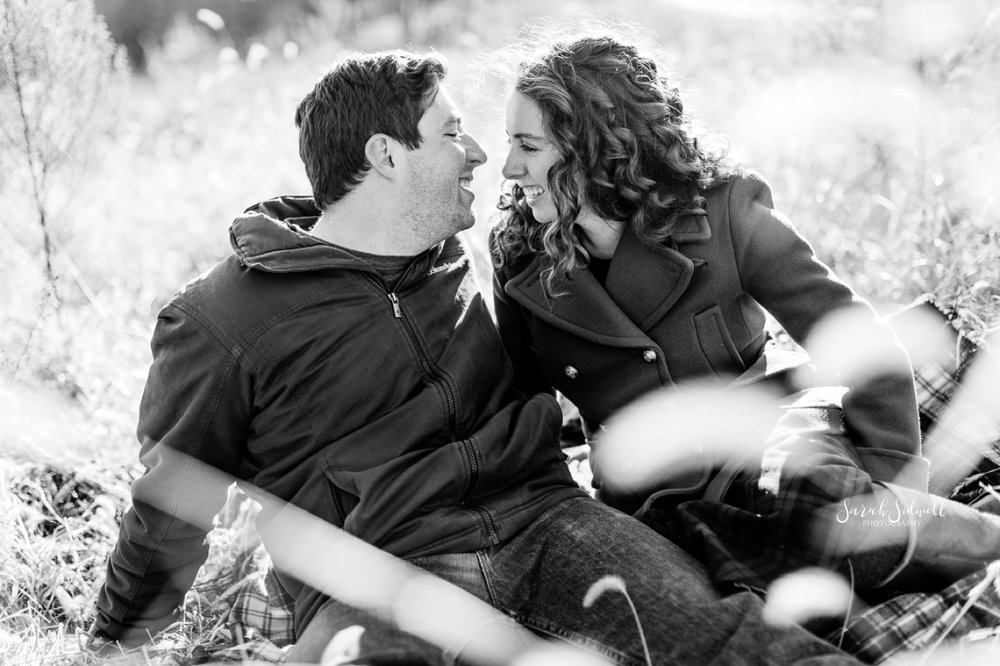 A couple laugh together during their photo shoot by an Engagement Photographer in Nashville.