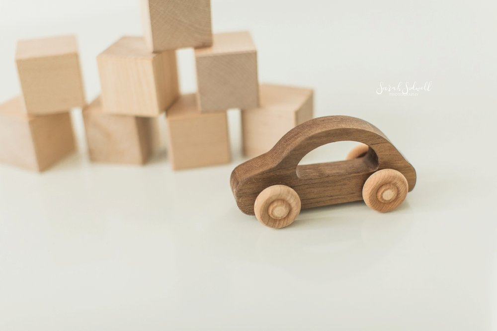 Wooden toys are sitting on a white floor.