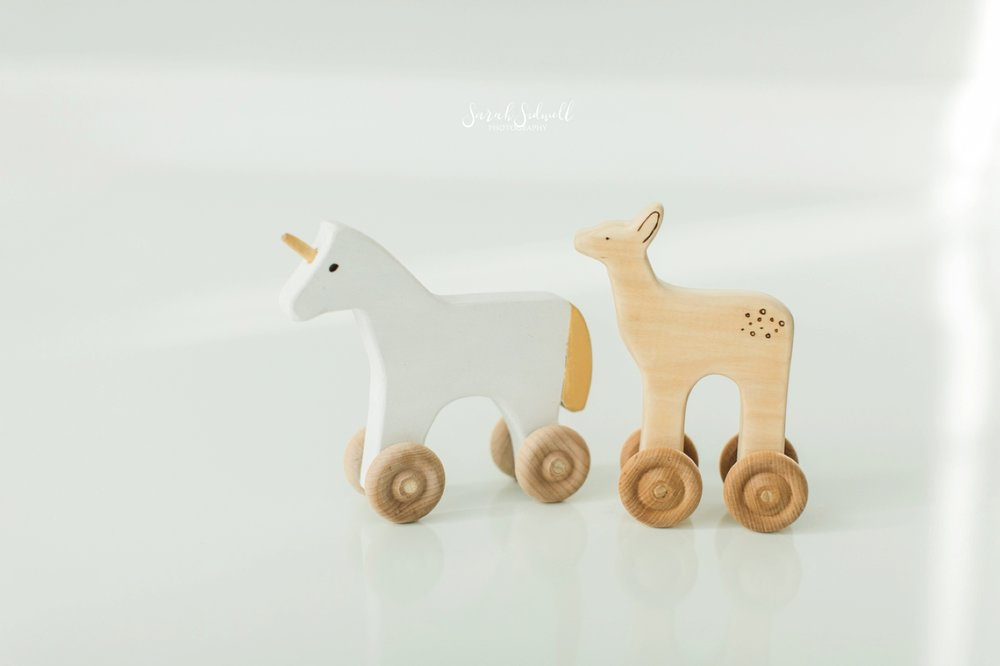 Wooden toy horse are displayed on a floor.
