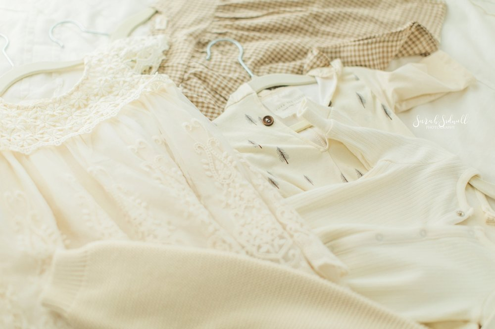 Cream colored clothing is laid out on a floor.