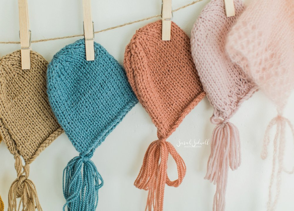 Knitted baby hats are pinned to a clothes line.