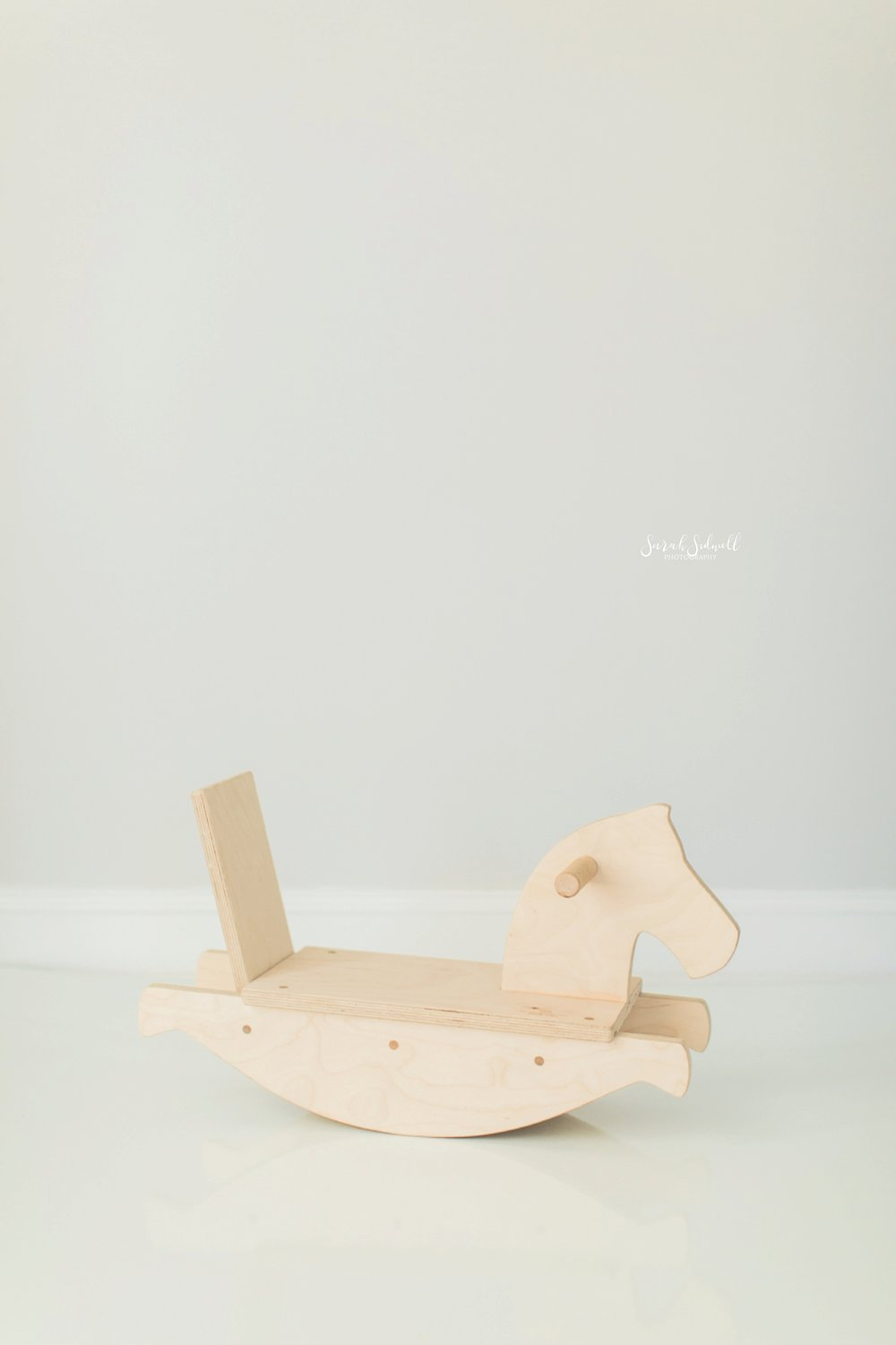 A wooden rocking horse is sitting in a white room.
