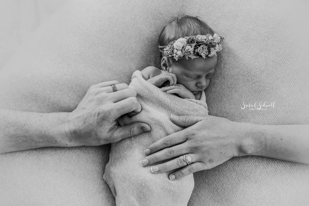 Two adult hands rest on a sleeping newborn.