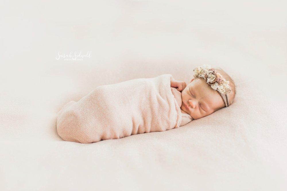 A baby sleeps while swaddled.