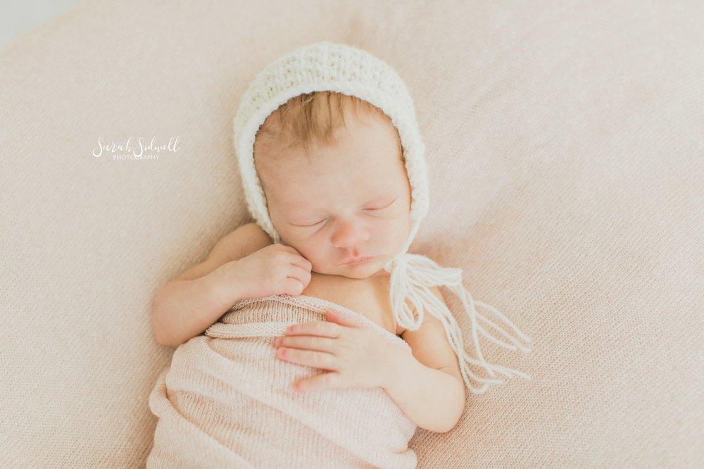 A baby wears a bonnet.