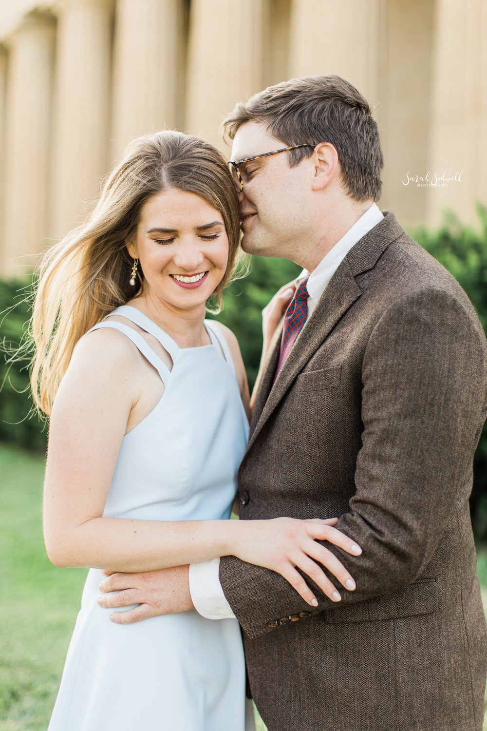 A man whispers into his fiance's ear.