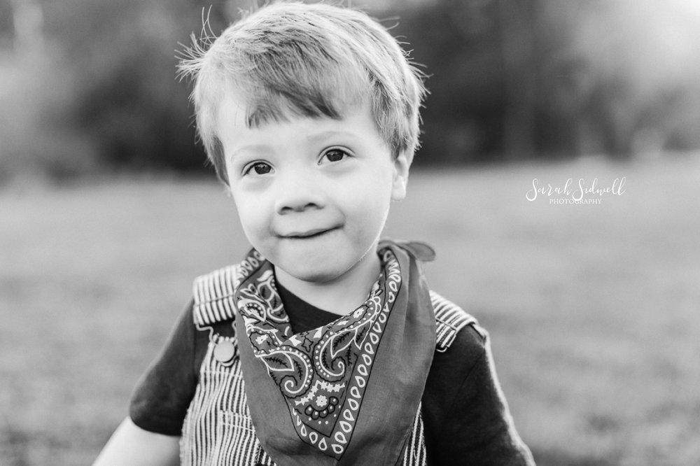 A boy smiles while wearing a bandanna.