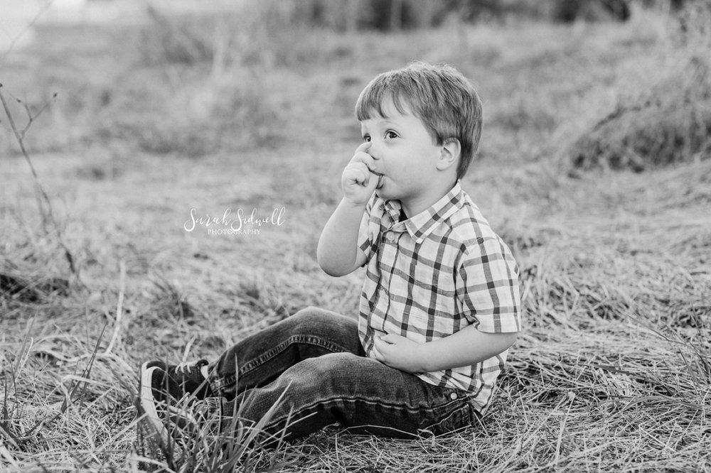 A boy sits in the grass.