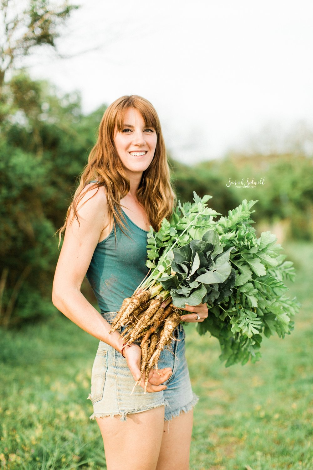 A woman holds a bunch of carrots.