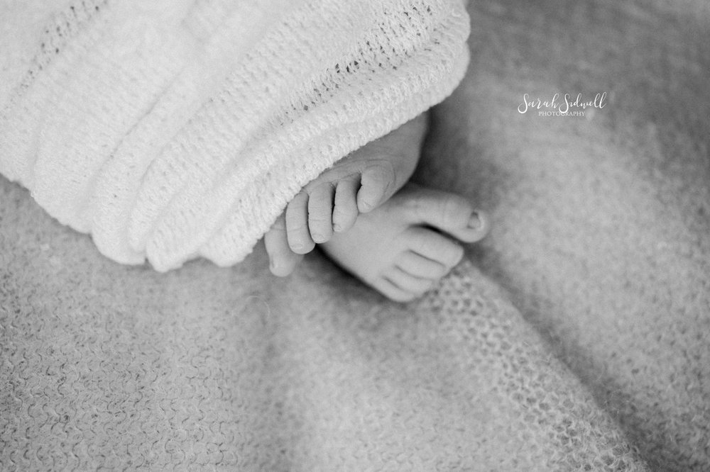 A baby's feet peek out of a blanket.