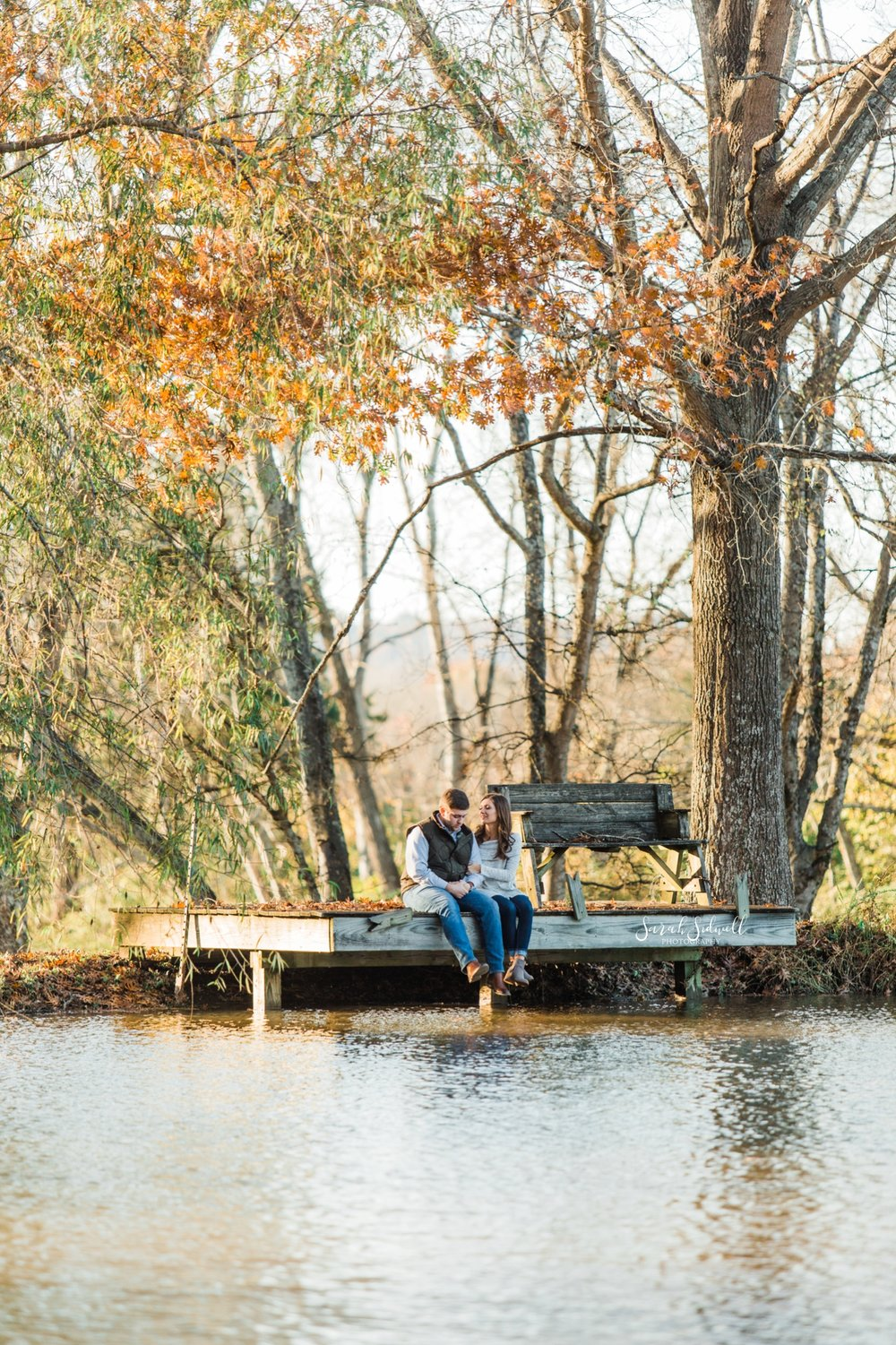 An engaged couple sit on a dock near a lake | Engagement Photography Nashville
