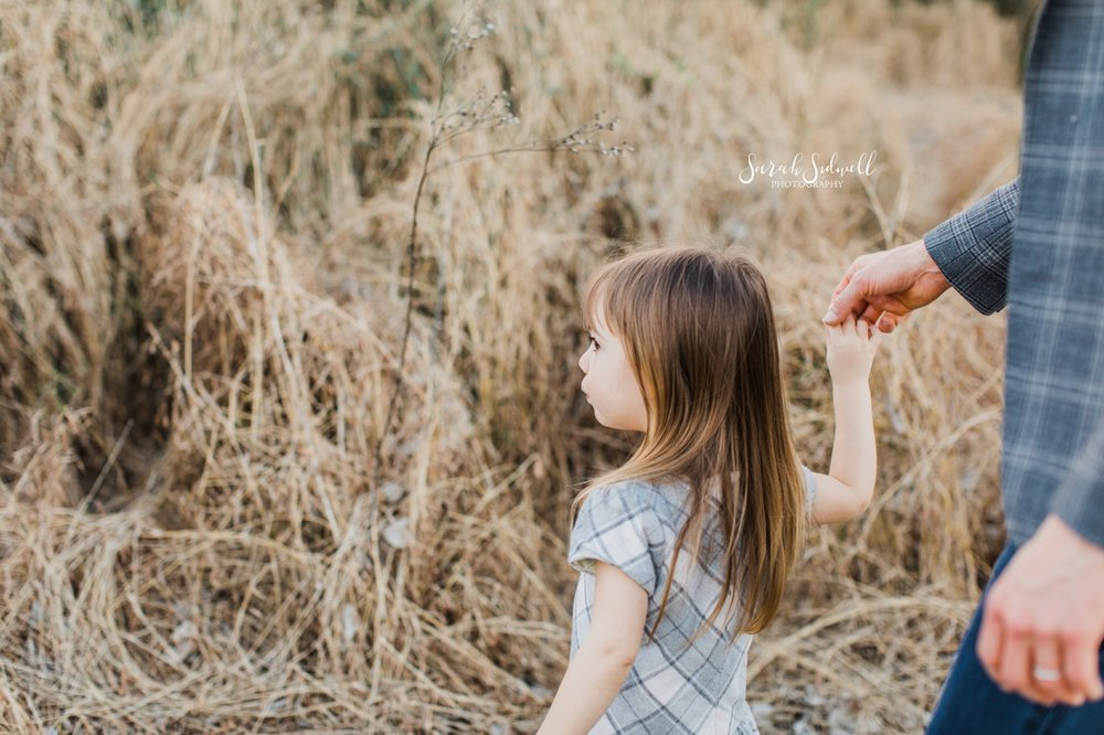 A girl holds her dad's hand.