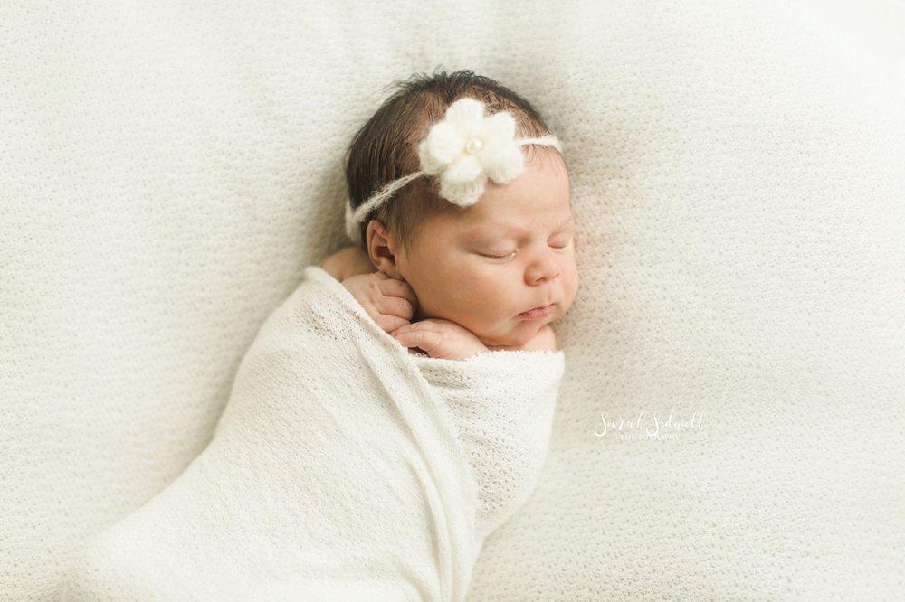 A newborn wears a flower headband.